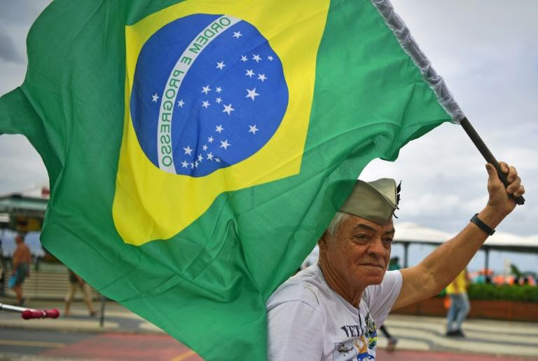 A supporter of President Jair Bolsonaro waves a Brazilian flag during a demonstration in support of the ultraconservative government as it faces growing opposition