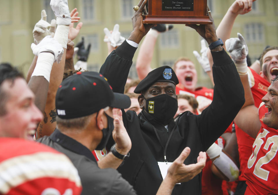 VMI Superintendent Maj. Gen. Cedric T. Wins lifts the Silver Shako Trophy after they defeated The Citadel in an NCAA college football game, Saturday, April 17, 2021, in Lexington, Va. (David Hungate/Roanoke Times via AP)