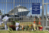 Flowers are laid on makeshift memorial is seen in front of cruise ship Ovation of the Seas, in Tauranga, New Zealand, Tuesday, Dec. 10, 2019. A volcanic island in New Zealand erupted Monday Dec. 9 in a tower of ash and steam while dozens of tourists were exploring the moon-like surface, killing multiple people and leaving many more missing.(AP Photo/Nick Perry)