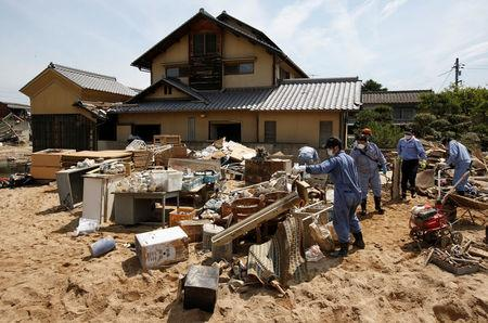 Local residents try to clear mud and debris from a house at a flood affected area in Mabi town in Kurashiki, Okayama Prefecture, July 13, 2018. REUTERS/Issei Kato