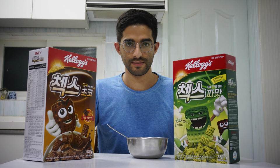 Journalist Raphael Rashid poses with two cereal boxes, including the new green onion flavored Chex cereal, in Seoul, South Korea, on Wednesday, July 1, 2020. The cereal has become a sensation in South Korea after 16 years of delay in its release. (AP Photo/Juwon Park)