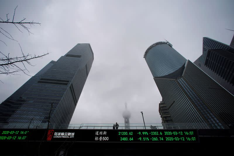 People are seen on a pedestrian overpass with an electronic board showing the Dow Jones and S&P 500 indexes, following an outbreak of the novel coronavirus in the country, at Lujiazui financial district in Shanghai