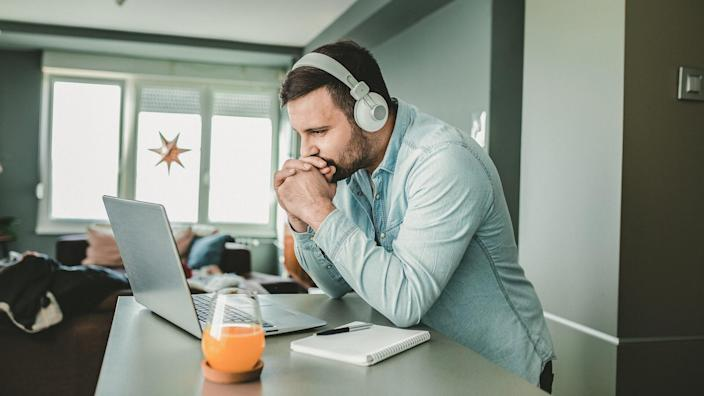 Young man is at home, with headphones and watching a online course.