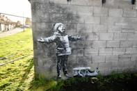 Artwork by street artist Banksy, which has appeared on a garage wall in Taibach, Port Talbot, south Wales. The painting appeared overnight and shows a child playing in the falling ash and smoke from a fire in a skip.
