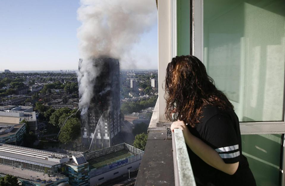 An onlooker watches as smoke pours from the Grenfell Tower (SWNS)