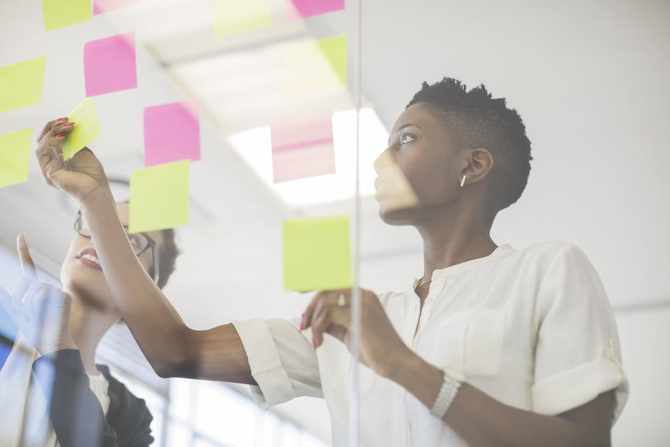 Businesswomen discussing over sticky notes on glass wall. Multi-ethnic female professionals are making strategy in creative office. They are wearing smart casuals.