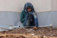 FILE PHOTO: An internally displaced Syrian girl with an amputated leg checks her phone at the Bab Al-Salam refugee camp, near the Syrian-Turkish border