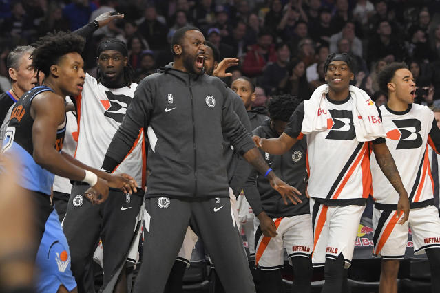 Members of the Los Angeles Clippers celebrate from the bench after center Ivica Zubac dunked as Cleveland Cavaliers guard Collin Sexton, left, walks away during the second half of an NBA basketball game Tuesday, Jan. 14, 2020, in Los Angeles. The Clippers won 128-103. (AP Photo/Mark J. Terrill)