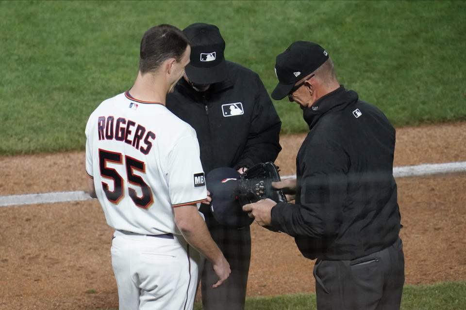 Minnesota Twins relief pitcher Taylor Rogers (55) gets a cap and glove check for sticky substances by umpires after throwing against the Cincinnati Reds in a baseball game, Monday, June 21, 2021, in Minneapolis. (AP Photo/Jim Mone)