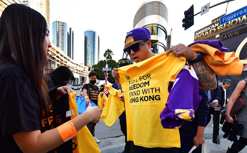 "Hong Kong supporters hand out free t-shirts outside Staples Center ahead of the Lakers vs Clippers NBA season opener in Los Angeles on October 22, 2019. - Activists handed out free T-shirts displaying support for the Hong Kong protests after an NBA fan in Northern California raised enough money to pay for more than 10,000 shirts, according to the organizer who goes by the pseudonym ""Sun Lared"" as LeBron James of the Lakers suffers the brunt of people's anger after comments he made in response to the tweet from Houston Rockets GM Daryl Morey in support of Hong Kong protesters, and drawing the ire of the Chinese Communist Pary. (Photo by Frederic J. BROWN / AFP) (Photo by FREDERIC J. BROWN/AFP via Getty Images)"