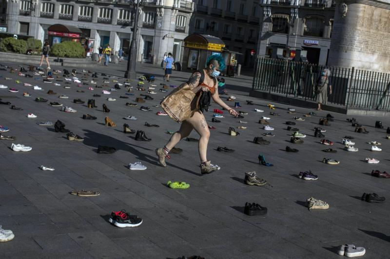 A woman with blue hair carries a paper bag and a pair of shoes as she steps among hundreds of pairs of shoes laid out in a grid in the public square.