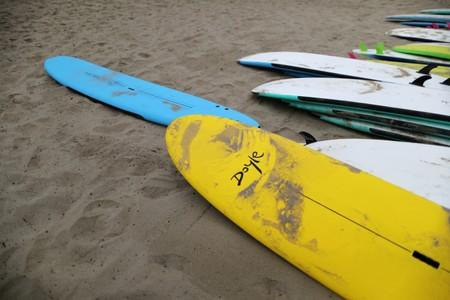 Doyle surfboards lie on the beach at a surf camp in Malibu