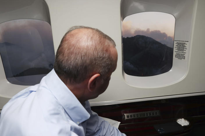 Turkey's President Recep Tayyip Erdogan watches from his plane the wildfires in Marmaris, Mugla, Turkey, Saturday, July 31, 2021. Panicked tourists in Turkey hurried to the seashore to wait for rescue boats Saturday after being told to evacuate some hotels in the Aegean resort of Bodrum due to the dangers posed by nearby wildfires, Turkish media reported. The death toll from wildfires raging in Turkey's Mediterranean towns rose to six Saturday after two forest workers were killed, the country's health minister said.(Turkish Presidency via AP, Pool)