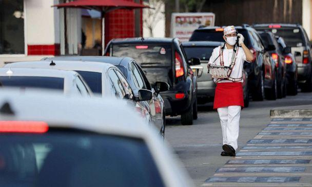 PHOTO: An employee wears a face covering while taking orders from motorists in the drive-through lane at an In-N-Out Burger restaurant amid the COVID-19 pandemic in Los Angeles, on July 1, 2020. (Mario Tama/Getty Images)