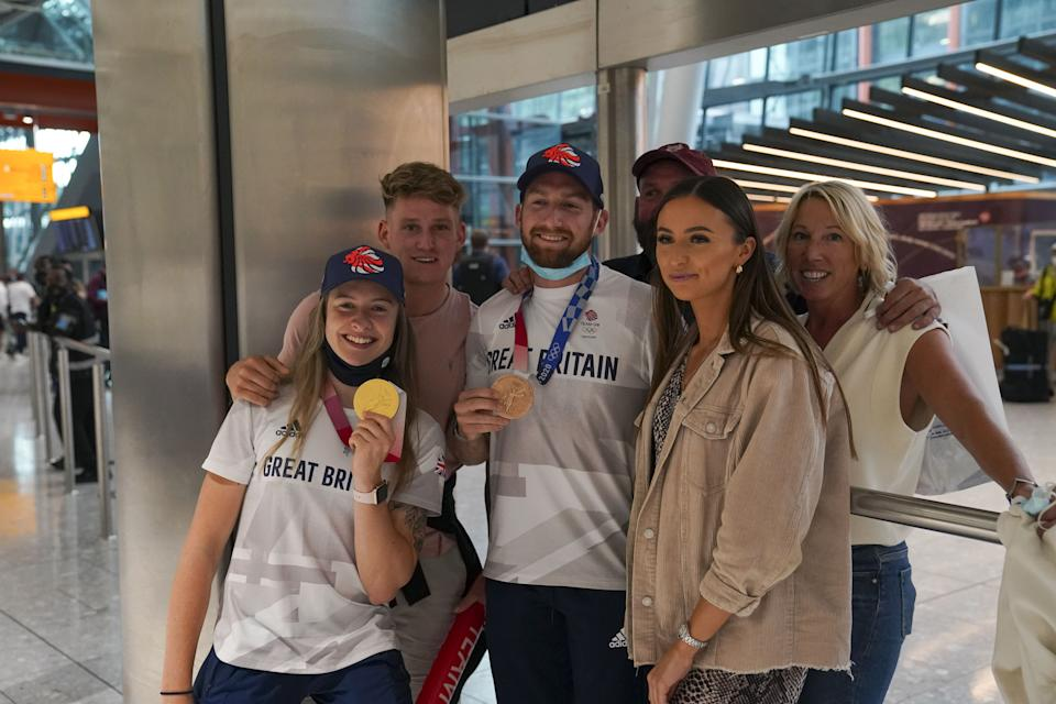 Charlotte Worthington (left) who won gold in the BMX Freestyle and Declan Brooks (centre) who won bronze arrive back at London Heathrow Airport from the Tokyo 2020 Olympic Games. Picture date: Tuesday August 3, 2021.