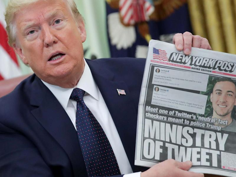 US president Donald Trump holds up a front page of the New York Post as he speaks to reporters while discussing an executive order on social media companies in the Oval Office of the White House in Washington, US, 28 May 2020: Jonathan Ernst/Reuters