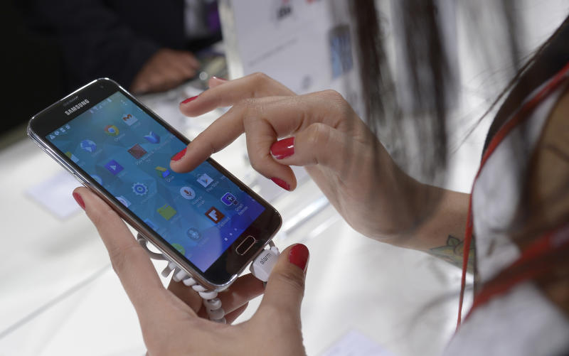 The new Samsung Galaxy S5 is displayed at the Mobile World Congress, the world's largest mobile phone trade show in Barcelona, Spain, Tuesday, Feb. 25, 2014. The phone will be at least the third to have a fingerprint sensor for security but it's alone in letting you use that for general shopping, thanks to a partnership with PayPal. (AP Photo/Manu Fernandez)
