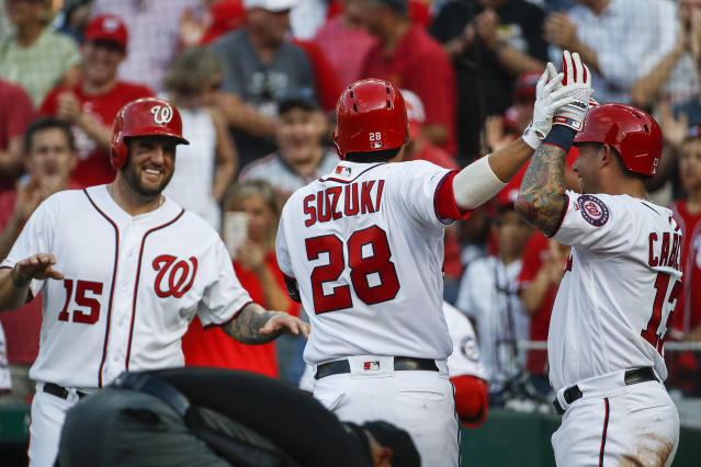 Washington Nationals catcher Kurt Suzuki celebrates his three-run homer with Matt Adams (15) and Asdrubal Cabrera during the fifth inning of a baseball game against the Cincinnati Reds at Nationals Park, Wednesday, Aug. 14, 2019, in Washington. (AP Photo/Alex Brandon)