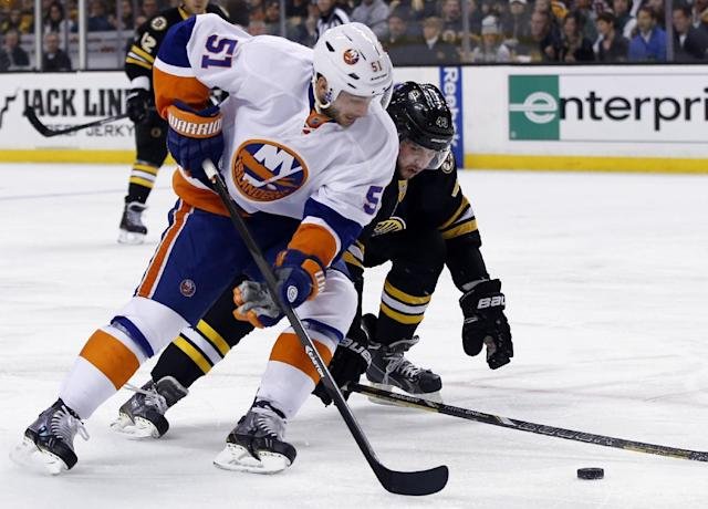 Boston Bruins defenseman Matt Bartkowski , right, tries to keep New York Islanders center Frans Nielsen (51) from getting a shot on goal during the first period of an NHL hockey game in Boston, Tuesday, Dec. 31, 2013. (AP Photo/Elise Amendola)