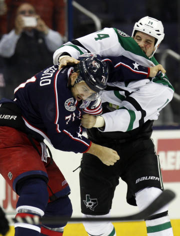Columbus Blue Jackets' Nick Foligno, left, and Dallas Stars' Jamie Benn fight during the second period of an NHL hockey game in Columbus, Ohio, Tuesday, Oct. 14, 2014. (AP Photo/Paul Vernon)