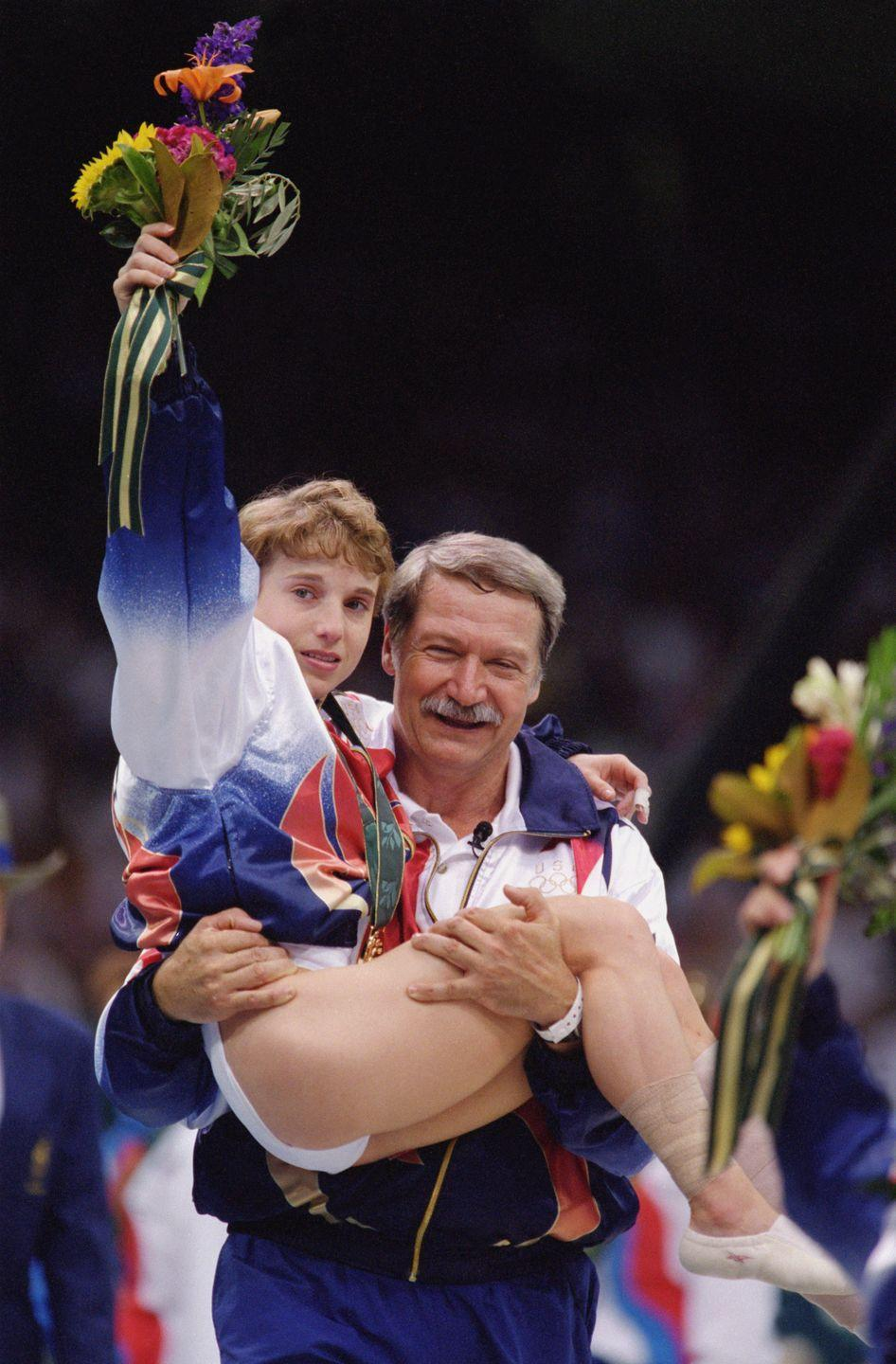 <p>Gymnast Kerri Strug helped the United States' Magnificent Seven clinch a win in the team all-around competition, even though it meant vaulting on an injured ankle. Coach Bela Karolyi carried her to the podium to claim her medal. </p>