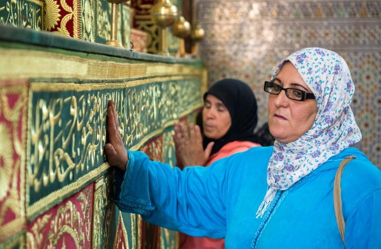 Pilgrims seek the blessing of Idriss I, a descendant of the Prophet Mohammed who founded Morocco's first Islamic dynasty, by placing a hand on his tomb or kissing it