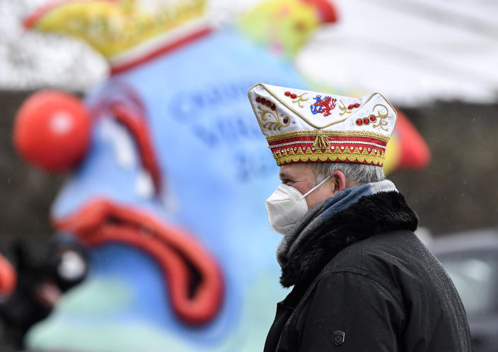 A reveller stands in front of political carnival floats to be shown in the streets of Duesseldorf, Germany, Monday, Feb. 15, 2021. Because of the coronavirus pandemic the traditional 'Rosenmontag' carnival parade are canceled but eight floats are pulled through the empty streets in Duesseldorf, where normally hundreds of thousands of people would celebrate the street carnival. (AP Photo/Martin Meissner)