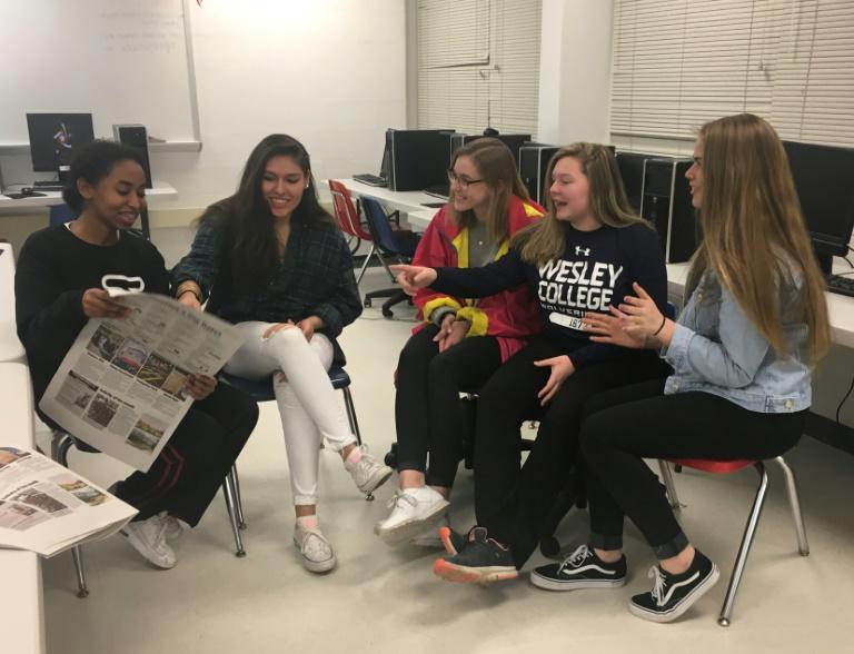 Nicole Uria (2nd L) sits with friends in Annandale, Virginia, where she is in her last year of high school, but fears her dreams of studying journalism in college my go unrealized