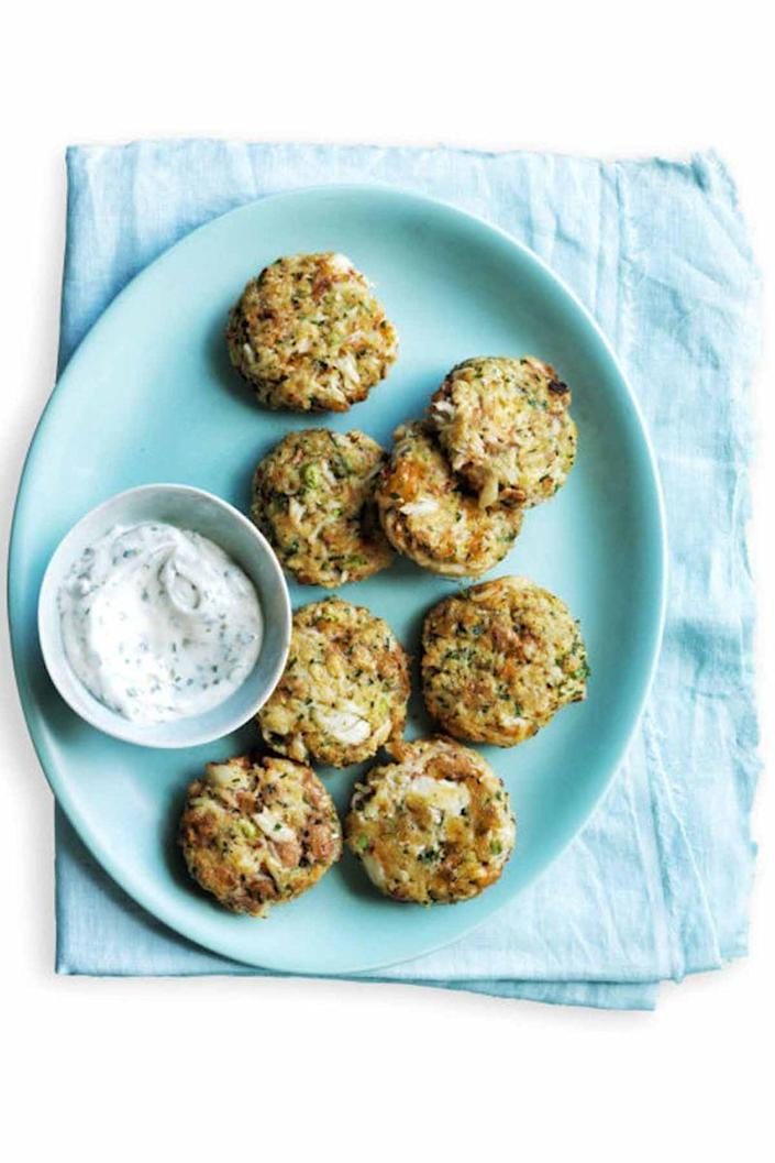 """<p>We guarantee your guests won't be able to resist snacking on these zesty crab cakes. </p><p><em><a href=""""https://www.womansday.com/food-recipes/food-drinks/recipes/a54836/zesty-mini-crab-cakes-recipe/"""" rel=""""nofollow noopener"""" target=""""_blank"""" data-ylk=""""slk:Get the Zesty Mini Crab Cakes recipe"""" class=""""link rapid-noclick-resp"""">Get the Zesty Mini Crab Cakes recipe</a>.</em></p>"""