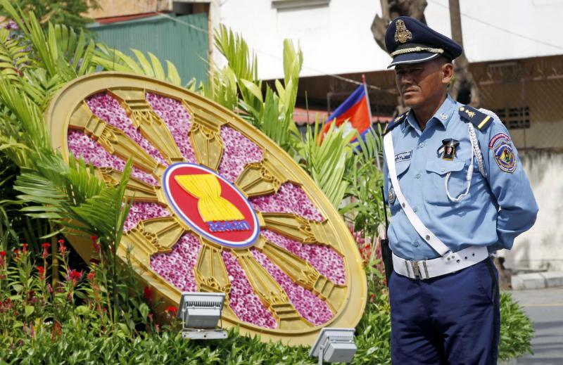 A Cambodian police officer stands next to a logo of Association of Southeast Asian Nations (ASEAN) in front of the Peace Palace ahead of the ASEAN Summit and related meetings in Phnom Penh, Cambodia, Saturday, Nov. 17, 2012.  (AP Photo/Vincent Thian)