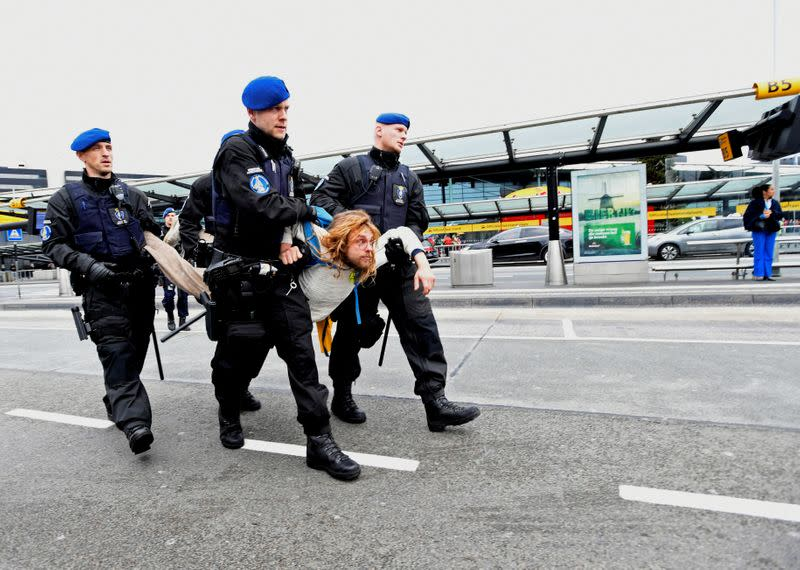 A protester is detained as Greenpeace stages a climate protest at Amsterdam Schiphol Airport in Schiphol