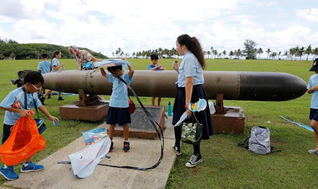 <p>Pupils play near the World War II remnants of a torpedo at the Asan Memorial Park on the island of Guam, a U.S. Pacific Territory, August 11, 2017. (Erik De Castro/Reuters) </p>