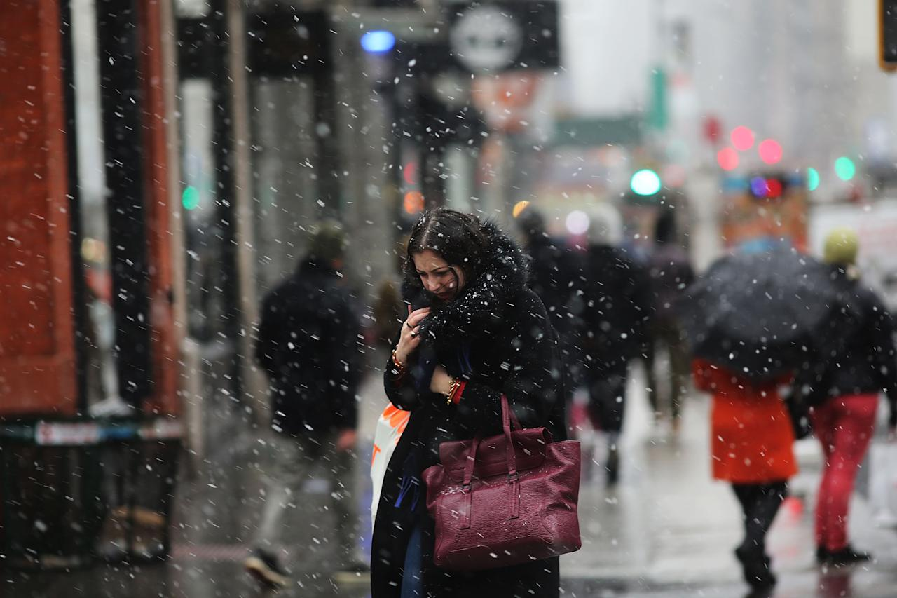 NEW YORK, NY - FEBRUARY 08:  A woman walks through wind, snow and sleet on Broadway as Manhattan prepares for a major winter storm on February 8, 2013 in New York City.  New York City and much of the Northeast is expected to get a foot or more of snow through Saturday afternoon with possible record-setting blizzard conditions expected. Heavy snow warnings are in effect from New Jersey through southern Maine.  (Photo by Spencer Platt/Getty Images)