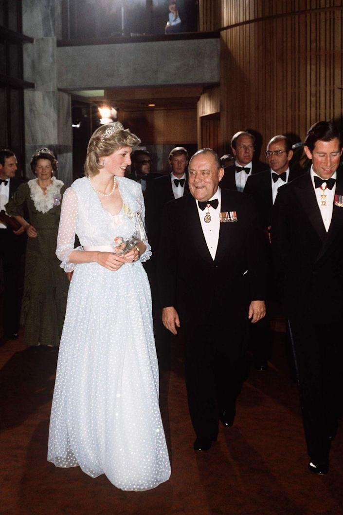 <p>Diana wears a dress designed by the Emanuels, who made her wedding gown, at a state Banquet in New Zealand. She's joined by the Prime Minister of New Zealand, Robert Muldoon, and Prince Charles.</p>