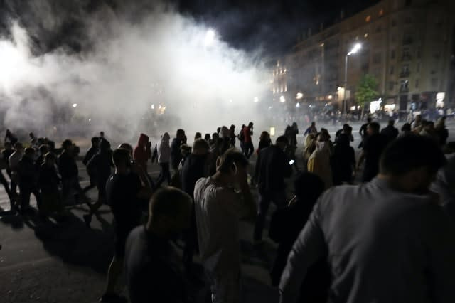Protesters run from tear gas in front of the Serbian parliament building in Belgrade, (Darko Vojinovic/AP)