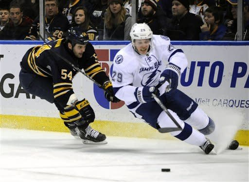 Buffalo Sabres' Zach Kassian (54) battles for the puck with Tampa Bay Lightning' Brendan Mikkelson (29) during the first period of an NHL hockey game in Buffalo, N.Y., Saturday, Feb. 11, 2012. (AP Photo/Gary Wiepert)