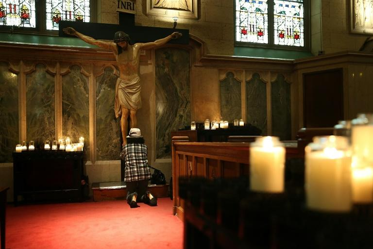 A woman prays at the foot of a statue of Jesus Christ inside a church in San Francisco