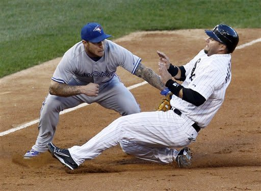 Toronto Blue Jays third baseman Brett Lawrie, left, tags out Chicago White Sox's A.J. Pierzynski at third, as Pierzynski tries to advance on a fielder's choice hit by Orlando Hudson to shortstop Yunel Escobar, during the second inning of a baseball game, Tuesday, June 5, 2012, in Chicago. (AP Photo/Charles Rex Arbogast)