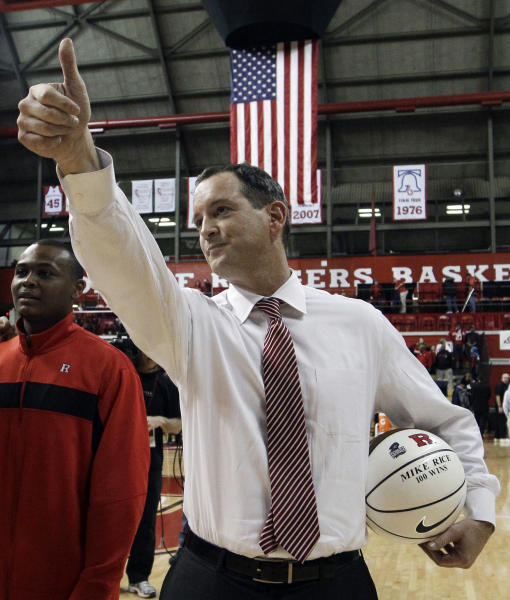FILE - In this Jan. 28, 2012, file photo, Rutgers coach Mike Rice waves as he holds a ball presented to him for his 100th career win after Rutgers defeated Cincinnati in an NCAA college basketball game in Piscataway, N.J. ESPN's airing on Tuesday, April 2, 2013, of a videotape of Rutgers basketball coach Mike Rice using gay slurs, shoving and grabbing his players and throwing balls at them in practice over the past three seasons has the university's athletic director reconsidering his decision not to fire the coach. Scarlet Knights AD Tim Pernetti was given a copy of the video in late November by a disgruntled former employee, and he suspended Rice for three games, fined him $50,000 and made him undergo anger management classes for inappropriate behavior after investigating it. (AP Photo/Mel Evans,file)