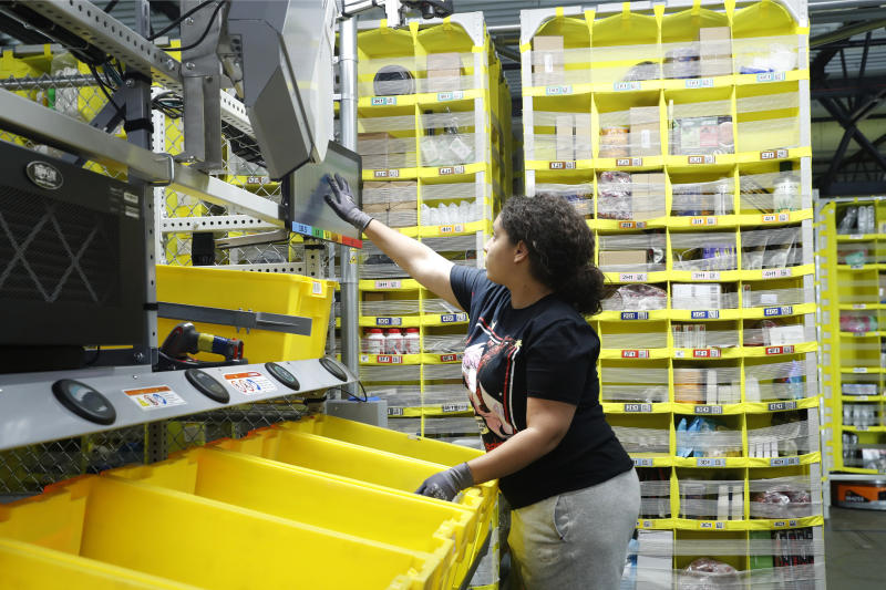 FILE - In this June 26, 2019, file photo a worker sorts through items and places orders at the Amazon Fulfillment Center in Staten Island in New York. Amazon.com Inc. reports financial earns on Thursday, Oct. 24. (AP Photo/Kathy Willens, File)