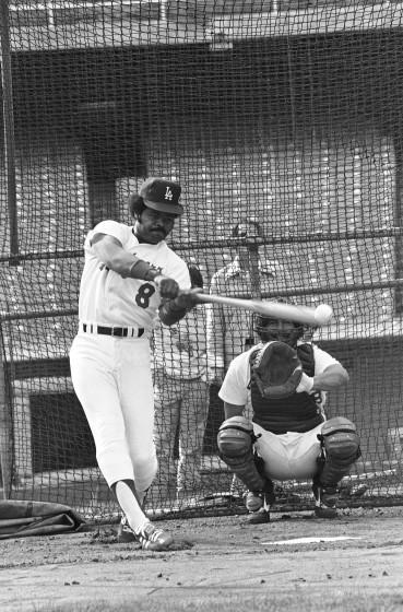 """Dodgers outfielder Reggie Smith socks one away from bullpen catcher Mark Cresse on Jan. 19, 1978, in Los Angeles during the team's opening workout. <span class=""""copyright"""">(Associated Press)</span>"""