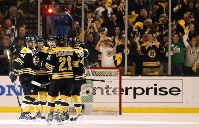 Boston fans cheer as Boston Bruins' Justin Florek, second from left, is congratulated by teammates Andrej Meszaros (41) and Loui Eriksson after scoring against the Detroit Red Wings during the first period of Game 2 of a first-round NHL hockey playoff series in Boston Sunday, April 20, 2014. (AP Photo/Winslow Townson)