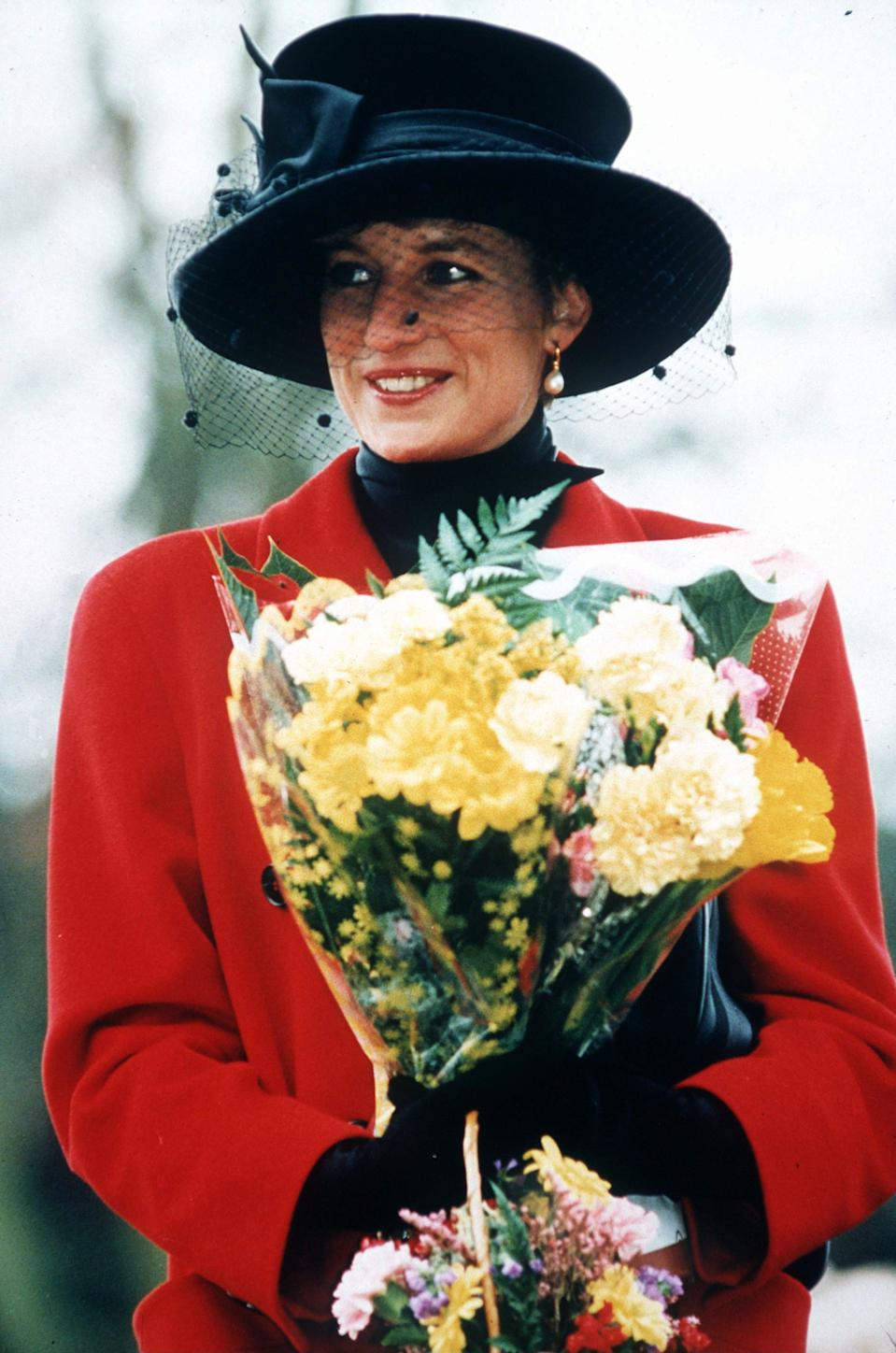 Princess Diana in a red coat and black hat at Sandringham on Christmas Day
