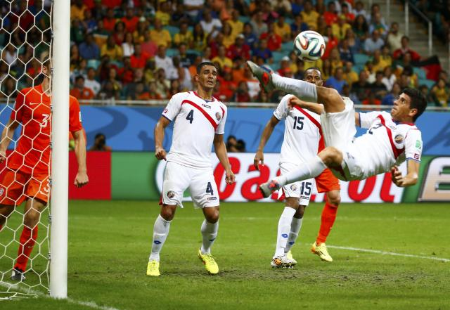 Costa Rica's Johnny Acosta (R) attempts an overhead kick to clear the ball from the penalty box during a Netherlands corner during their 2014 World Cup quarter-finals at the Fonte Nova arena in Salvador July 5, 2014. REUTERS/Paul Hanna (BRAZIL - Tags: SOCCER SPORT WORLD CUP)
