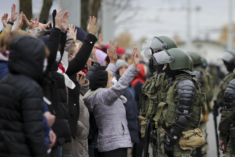 Demonstrators stand with their hands up in front of riot police line during an opposition rally to protest the official presidential election results in Minsk, Belarus, Sunday, Nov. 1, 2020. Some thousands of protesters swarmed the streets of the Belarus' capital on Sunday, demanding the resignation of the country's longtime authoritarian leader, and were met with police firing warning shots into the air and using stun grenades to break up the crowds. (AP Photo)