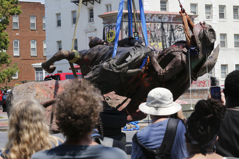 FILE - This Tuesday July 7, 2020, file photo shows crews at they lower the statue Confederate General J.E.B. Stuart in preparation for transport after removing it from it's pedestal on Monument Avenue in Richmond, Va. Devon Henry, whose company handled the summer removals of Richmond's Confederate monuments, spoke with The Associated Press about navigating safety concerns for himself and his crew and previously unreported complexities of the project. (AP Photo/Steve Helber)