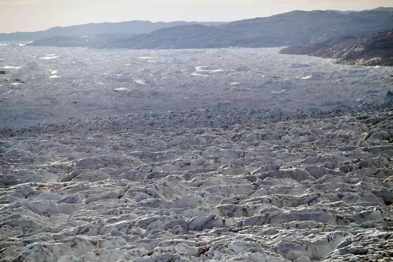In this July 19, 2011 photo, rows of pressure ridges stack up, foreground, before tumbling over the ever-collapsing calving 6-kilometer- (4-mile-) wide front of Jakobshavn Glacier and into the Ilulissat ice fjord, background, in Greenland. (AP Photo/Brennan Linsley)