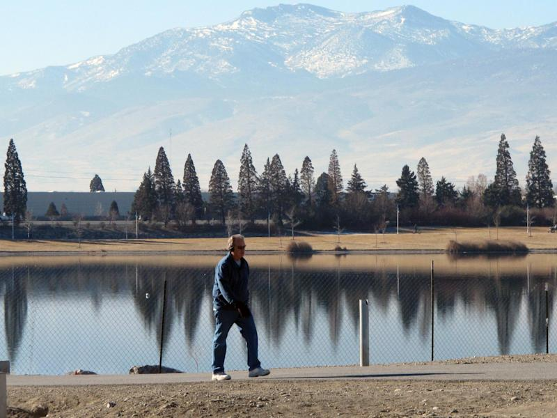 An unidentified man walks on the 2-mile loop trail surrounding the Sparks Marina, where all of the fish have died over the past month _ an estimated total of 100,000 trout, bass and catfish _ on Friday, Jan. 17, 2014, in Sparks, Nev. Scientists say a sudden cold spurt in December likely caused a violent ``turnover'' of the 77-acre, man-made lake's waters that sucked out almost all the oxygen and killed the fish. (AP Photo/Scott Sonner).
