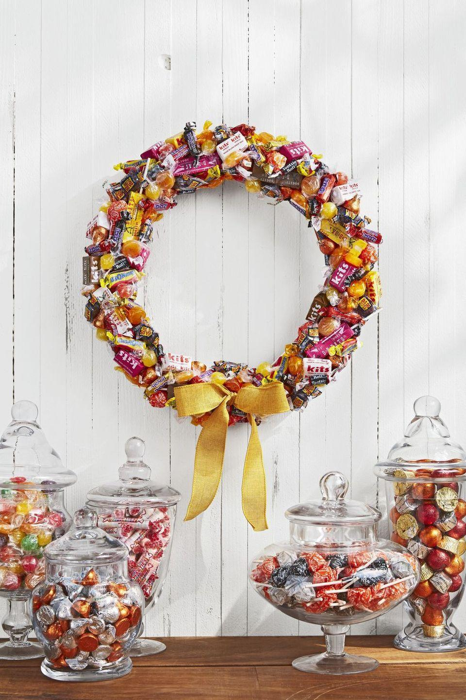 <p>Try not to eat this delicious-looking wreath, and it can decorate your door all season long.<strong><br></strong></p><p><strong>Make the wreath:</strong> Gather an assortment of old-fashioned candies in autumnal shades such as yellow, orange, and magenta. Wrap a 14-inch foam wreath form in white ribbon. Attach candy with hot-glue, layering and overlapping as you go. Finish with a yellow burlap bow. </p>