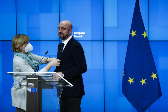 A make up assistant adjusts the tie of European Council President Charles Michel prior an online joint press conference with Director General of the World Health Organization Tedros Adhanom Ghebreyesus at the European Council headquarters in Brussels, Tuesday, March 30, 2021. (AP Photo/Francisco Seco, Pool)